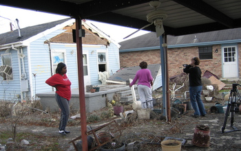 Three women next to houses damaged by storm