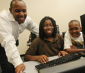 Photo of Kevin Clark and students at a computer.