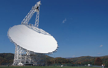 Telescope's broad white dish aims upward at a nearly cloudless sky.