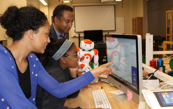 students and professor with robot and a computer