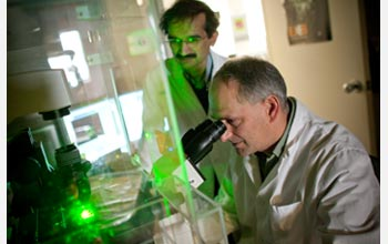 Photo of Himanshu Jain and a colleague examining materials in a laboratory.