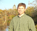 Photo of John Rothlisberger standing in front of one of the lakes on Notre Dame's campus.