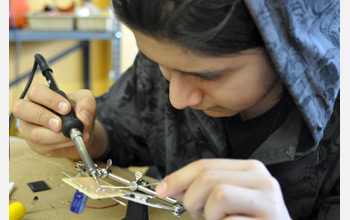 Photo of a student soldering together a solar powered robot.