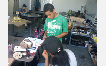 Photo of Jose working on his homemade robot.