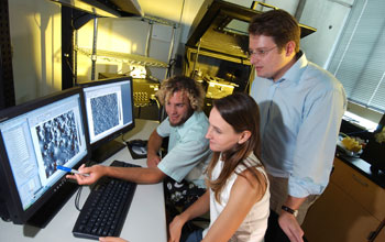Photo of grad students and assistant professor working on nanometer-scale patterns on a computer