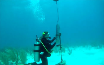 researcher under water holding a recording device.