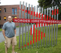 GROW student Erich Petushek standing next to a sign at the Norwegian School of Sports Sciences