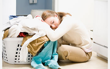 Photo of woman resting her head on basket of laundry.