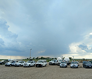 multiple vehicles in an open field under a daunting sky