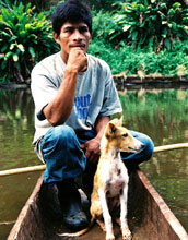Image of a Mayangna hunter and his dog resting in a dugout canoe.
