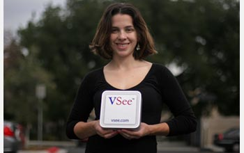 Photo of Colleen Beeson of VSee holding the hardware component of their virtual office system.