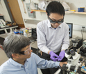Delaware EPSCoR researcher Juejun Hu holds a sensor chip, while Chaoying Ni looks on.