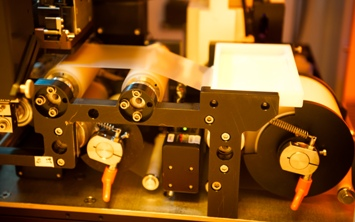 Photo of a plastic substrate moving over two rollers for nano-sculpting.