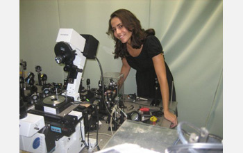Photo of Markita Landry standing with a Total Internal Reflection Fluorescence Microscope.