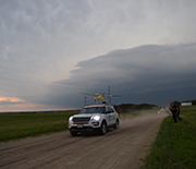 a vehicle traveling on a dirt road with a stormy sky