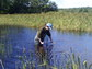 Scientist in lake collecting sediment samples in Maine