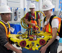 Photo of three Long Beach City College ROV Team members transporting their vehicle from the pool.
