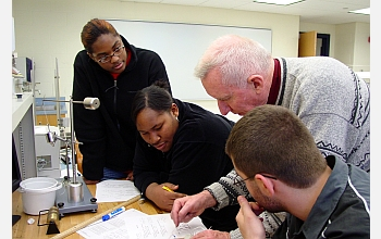 12th-grade physics students work with teacher.