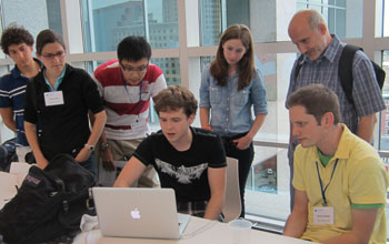 Undergraduate students with faculty leader, Sergei Tabachnikov, working on a computer