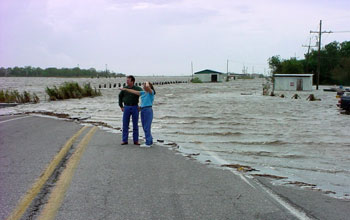 Image of two people standing next to a flooded highway in Louisiana.