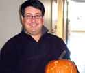 Photo of Lyle Isaacs holding a pumpkin with the chemical structure of the CB[n] molecule.