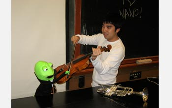 Photo of Ryan Miyakawa warming up the orchestra before recording The Nano Song.