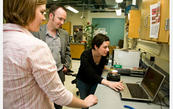 Photo of Charles Sykes and graduate students looking at images of molecules on a computer screen.