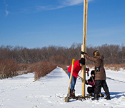 Three researchers install a nest box in a field.