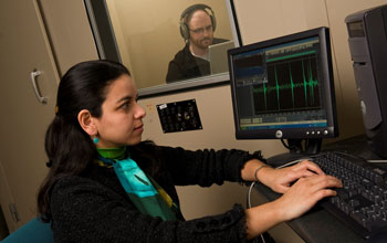 Photo of researcher and a colleague in a sound booth using a computer to record sound