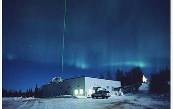 Photo of the aurora and a laser radar beam lighting up the sky at the Lidar Research Laboratory.