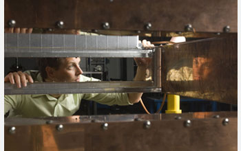 Photo of Matt Johnson, NSCL staff engineer, inspecting a 45-degree dipole magnet