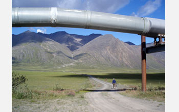 Photo of Andrew Jacobson and colleague hiking along a road with Alaskan pipeline in foreground.
