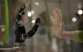 Human hand held up to a plate of glass, with a robotic hand mirroring the same gesture on the other side of the glass