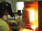 Photo of Amy Barnes making phosphorus-rich phosphate glass to use with her doctoral research work.