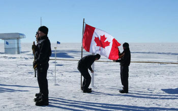 A memorial ceremony in Antarctica showing people and the Canadian flag.