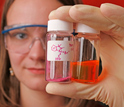 Photo of Deana Hadley displaying bottles of conjugated polymers.