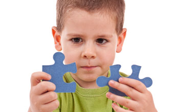 Photo of a child holding two puzzle pieces.