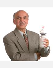 Photo of G.K. Surya Prakash holding a liquid-methanol fuel cell.