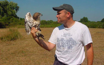 Photo of Professor James Hewlett with a juvenile male red-tailed hawk.