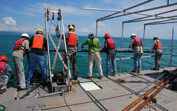 researchers on a ship doing sediment coring