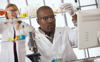 Photo of a male scientist in foreground holding test tube and pipette, female researcher in back.