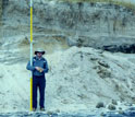 Scientist with measuring stick checks vertical erosion at the Cupsogue Beach, N.Y.