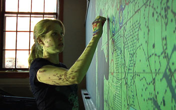 Image of a young woman marking a green screen on the wall.