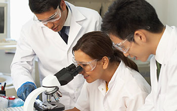 Photo of three scientists working in a laboratory.