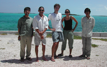 Photo of David Spiller, second from left, and other scientists posing on a beach in the Bahamas.