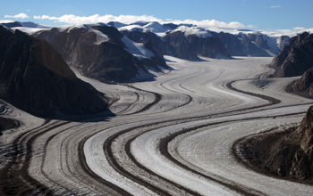Photo of a glacer with mountains on both sides and trails of rock and soil in the glacier.