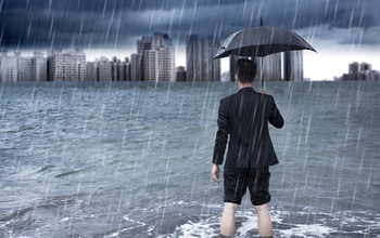 Man standing in floodwaters and holding an umbrella looks toward a city skyline.