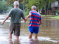Two men walk hand in hand through a flood-covered street.