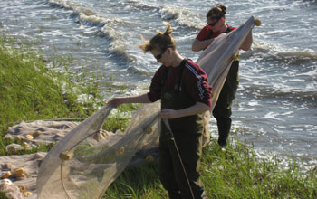 Photo of researchers Tara Duffy and Lora Clarke preparing a net for seining off South Carolina.