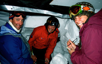 Photo of Noah Molotch, Danielle Perot and Ty Atkins studying snow properties from inside a snow pit.